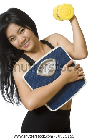 Attractive young Asian girl with weight scale and dumbbell - stock photo