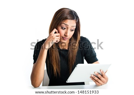 Attractive young Asian Indian teenage woman, working with a non-branded generic portable tablet looking concerned  - stock photo