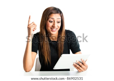 Attractive young asian indian teenage woman, working with a portable tablet computer looking angry and frustrated - stock photo