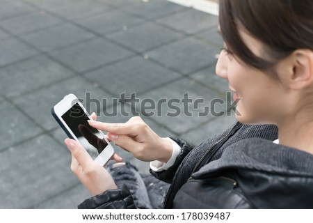 Attractive young Asian woman using smartphone, closeup portrait. - stock photo