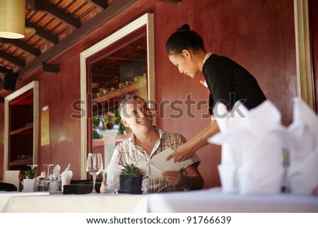 Attractive young asian woman working as waitress in exclusive restaurant and attending customer with menu - stock photo