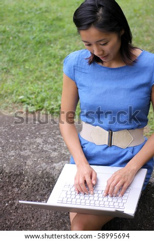 Attractive young Asian woman working outdoors with her laptop - stock photo