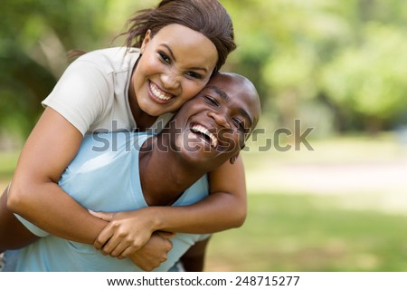 attractive young black couple piggybacking outdoors - stock photo
