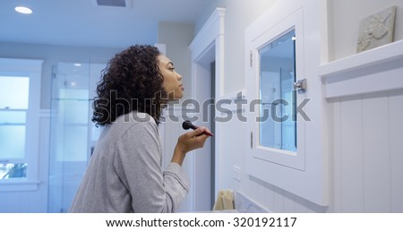 Attractive young black woman applying makeup - stock photo