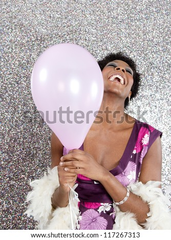 Attractive young black woman holding pink balloons against a silver glitter background, laughing. - stock photo