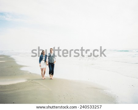 Attractive Young Blond Couple  on beach, walking, wide shot - stock photo