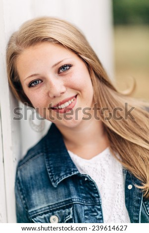 Attractive Young Blond leaning against white wall, looking at camera, smiling, jean jacket - stock photo