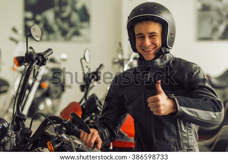 Attractive young blond man in black leather jacket and helmet is looking at camera, showing Ok sign and smiling while sitting on a motorbike - stock photo