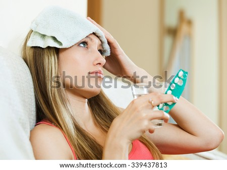 Attractive young blond take some pills, holds glass of water in home interior - stock photo