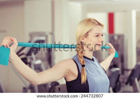Attractive young blond woman exercising in a gym stretching and toning her muscles in a health and fitness concept - stock photo