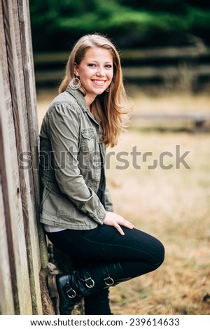Attractive Young Blond Woman in front of horse stable leaning against wall, smiling - stock photo