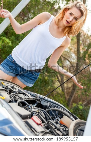 Attractive young blond woman inspecting her car engine after a breakdown at the roadside frowning in annoyance and frustration - stock photo