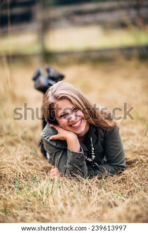 Attractive Young Blond Woman laying in straw feet up laughing, hand on shoulder, leaning over - stock photo