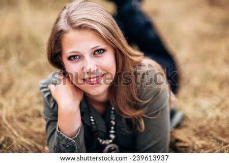 Attractive Young Blond Woman laying in straw feet up, slight smile close up variation - stock photo