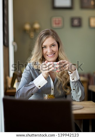 Attractive young blond woman sitting in cafe with warm drink - stock photo