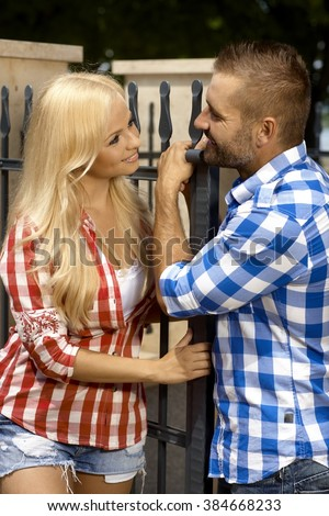 Attractive young blonde casual woman and stubbly handsome man outdoor, leaning against fence, smiling. - stock photo