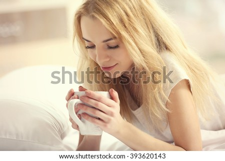 Attractive young blonde girl in a pajama enjoying her morning drink while laying in bed - stock photo