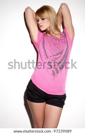 Attractive young blonde girl in black shorts and pink t-shirt posing sensually - stock photo