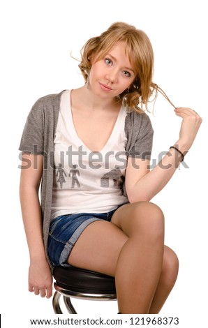 Attractive young blonde girl sitting on a stool in trendy denim shorts twirling her hair isolated on white - stock photo