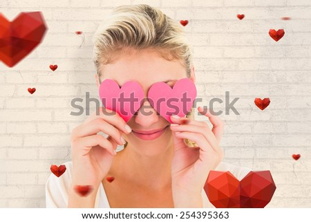 Attractive young blonde holding hearts over eyes against white wall - stock photo
