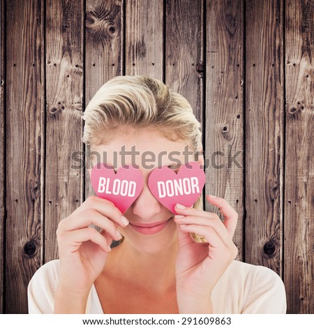 Attractive young blonde holding hearts over eyes against wooden planks background - stock photo