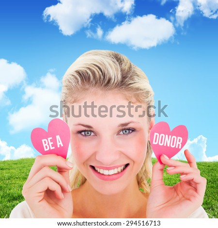 Attractive young blonde holding little hearts against blue sky over green field - stock photo