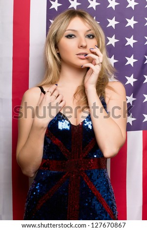 Attractive young blonde on a background of the American flag - stock photo