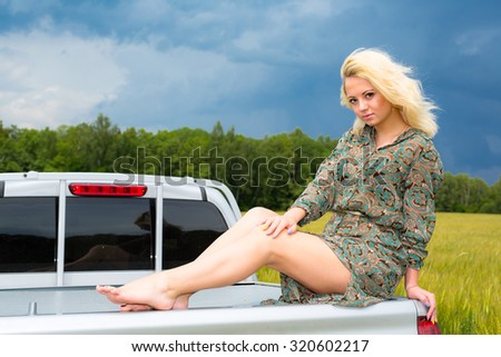 Attractive young blonde woman sitting on car - stock photo