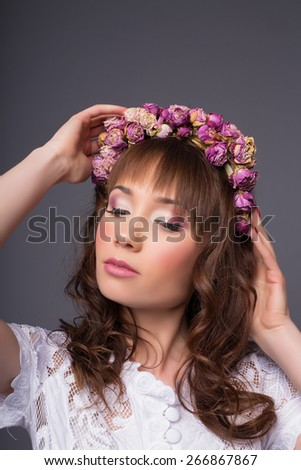 attractive young bride in studio straightens hair - stock photo