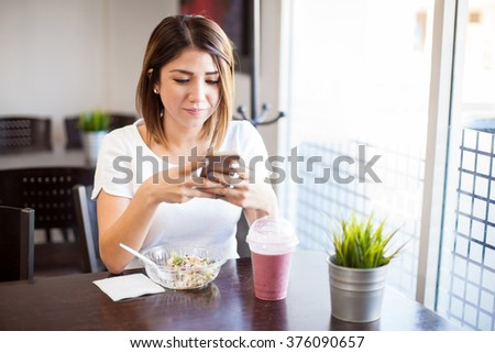Attractive young brunette eating some healthy food and using a smartphone in a restaurant - stock photo