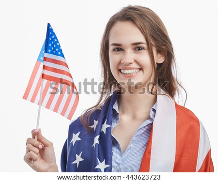 Attractive young brunette girl covered by National Flag celebrating Independence Day on 4th of July in United States of America.Cute model with toothy smile on isolated white background - stock photo