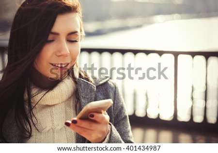 Attractive young brunette girl with long brown hair and friendly smile using a modern smart phone outdoors at bright spring day.  - stock photo