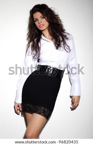 Attractive young brunette in black sexy dress and white shirt posing sensually - stock photo