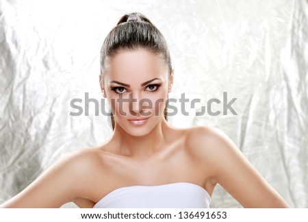 Attractive young brunette on silver background - stock photo