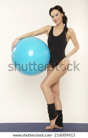 Attractive young brunette sporty woman in black dress with blue fitness ball isolated on white background - stock photo