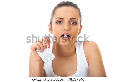 attractive young brunette takes some pills, isolated on white - stock photo