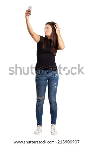Attractive young brunette taking high angle self photo or selfie with her smart phone.  Full body length isolated over white. - stock photo