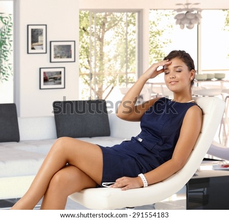 Attractive young brunette tired caucasian woman in blue dress resting in leather chair at trendy home. Smiling, caressing herself, eyes closed, relaxing. - stock photo