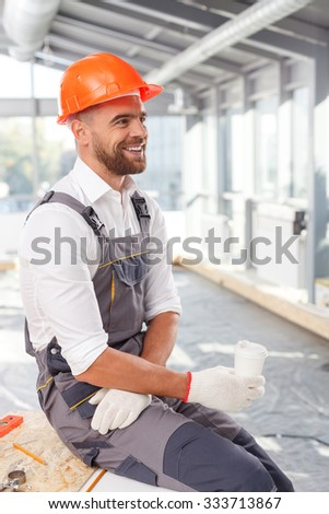 Attractive young builder is drinking coffee on break. He is sitting and smiling. The man is orange helmet is looking forward with happiness - stock photo