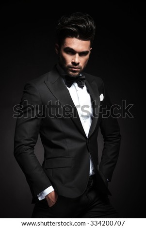 Attractive young business man looking at the camera while holding both hands in his pocket. - stock photo