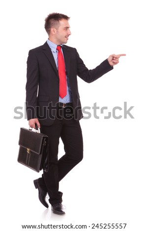 Attractive young business man pointing at something to his left while holding a black briefcase. - stock photo