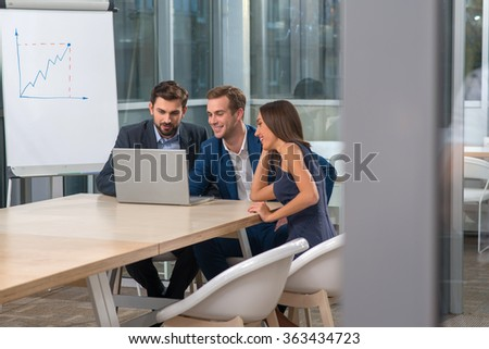 Attractive young business partners are communicating with their client through the laptop. They are sitting at the desk is conference office. The men are woman are smiling - stock photo