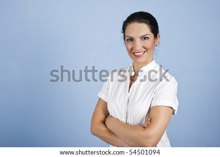 Attractive young business woman standing with arms crossed on blue background,copy space for text in left part of image - stock photo