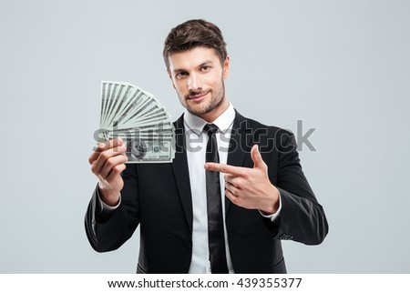 Attractive young businessman holding money and pointing on it over white background - stock photo
