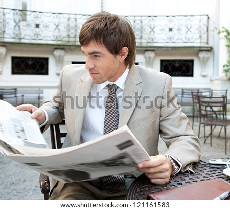 Attractive young businessman reading the newspaper while having a coffee and sitting at a coffee shop terrace in a classic office buildings city square. - stock photo