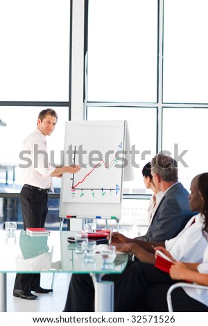 Attractive young businessman reporting to sales figures to his colleagues - stock photo