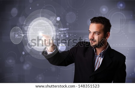 Attractive young businessman touching abstract high technology circular buttons - stock photo