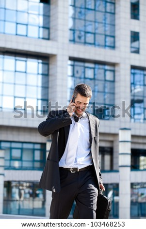 Attractive young businessman using a cell phone, smiling. Taken in front of a modern office building on a beautiful sunny day. - stock photo