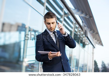 Attractive young businessman using a cell phone. Taken in front of a modern office building. - stock photo
