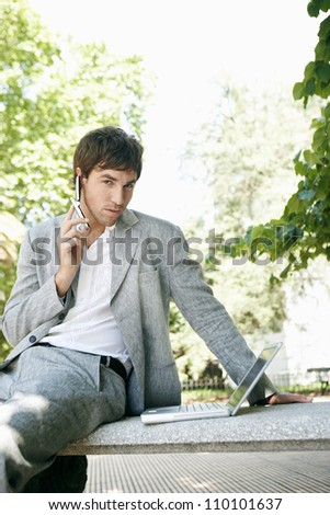 Attractive young businessman using different technology while sitting on a bench in the park. - stock photo